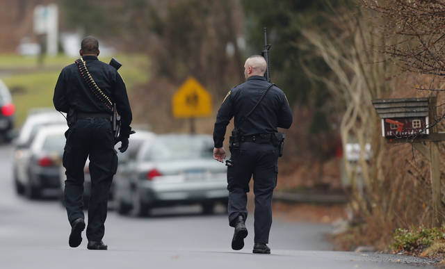 Police officers walk up to an elementary school, which was in a lockdown, in Ridgefield, Conn., Monday, Dec. 17, 2012, after a suspicious person was seen near the train station close to the school. On Friday, authorities say a gunman killed his mother at their home and then opened fire inside the Sandy Hook Elementary School in Newtown, killing 26 people, including 20 children, before taking his own life. (AP Photo/Charles Krupa)