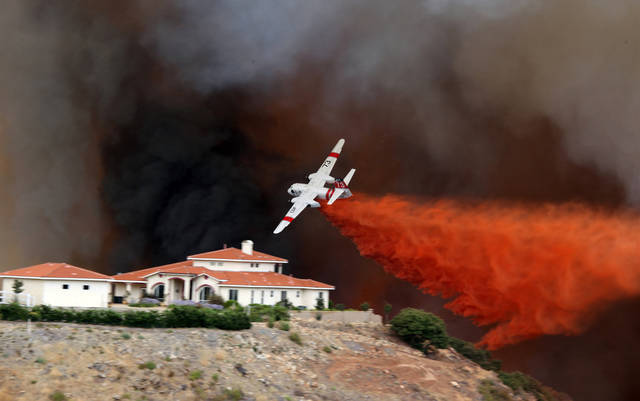 A firefighting air tanker drops fire retardant on a hillside as a wildfire rages, Wednesday Aug. 1, 2012 in Murrieta, Calif. AP photo