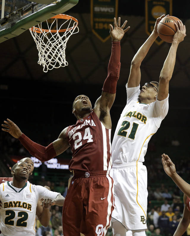 Oklahoma's Romero Osby (24) defends as Baylor's Isaiah Austin (21) goes up for a score in the second half of an NCAA college basketball game as Baylor's A.J. Walton (22) watches Wednesday, Jan. 30, 2013, in Waco, Texas. Oklahoma won 74-71. (AP Photo/Tony Gutierrez) ORG XMIT: TXTG111