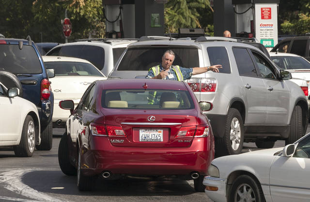 An attendant directs customers at the Costco gas station in Burbank, Calif., Friday, Oct. 5, 2012. Californians woke up to a shock Friday as overnight gasoline prices jumped by as much as 20 cents a gallon in some areas, ending a week of soaring costs that saw some stations close and others charge record prices. (AP Photo/Damian Dovarganes)