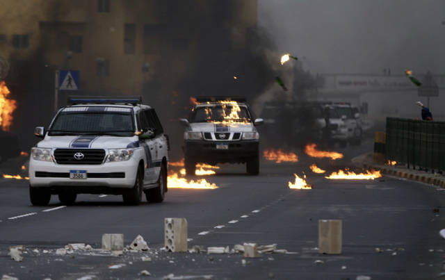 A Bahrain riot police convoy comes under Molotov cocktail attack by anti-government protesters Thursday, March 15, 2012, during heavy clashes in the eastern town of Sitra, Bahrain. The clashes erupted during protests marking the one-year anniversary of a major crackdown on Sitra, an area that has seen some of the strongest anti-government unrest. (AP Photo/Hasan Jamali)