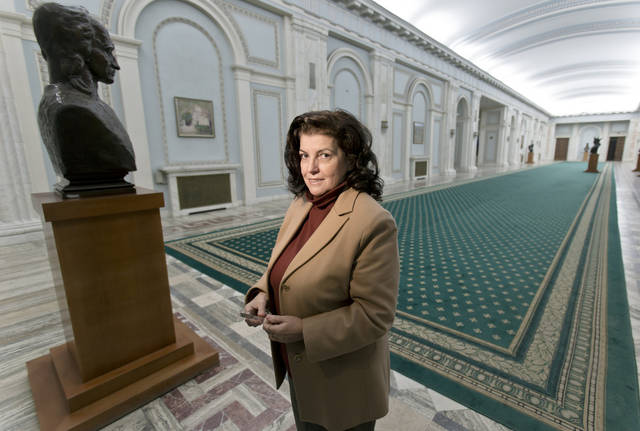 In this Nov. 16, 2012 photo, Anca Petrescu, the architect who designed the Parliament Palace, poses inside the building in Bucharest, Romania. Twenty-three years after communism collapsed, the Palace of the Parliament, a gargantuan Stalinist symbol and the most concrete legacy of ex-dictator Nicolae Ceausescu, has emerged as an unlikely pillar of Romania's nascent democracy. And while it remains one of the most controversial projects of Ceausescu's 25-year rule, albeit one that has gradually found a place in the nation's psyche, it's also now a tourist attraction, visited by tens of thousands of Romanians and foreigners every year. (AP Photo/Vadim Ghirda)