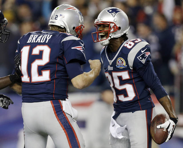 New England Patriots quarterback Tom Brady (12) celebrates his 37-yard touchdown pass to wide receiver Brandon Lloyd (85) during the first quarter of an NFL football game against the Houston Texans in Foxborough, Mass., Monday, Dec. 10, 2012. (AP Photo/Elise Amendola) ORG XMIT: FBO112
