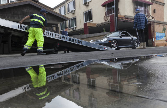 A Porsche Sports car is towed away after flood waters damaged its electric systems near the overflowed streets onto Pacific Coast Highway in the Sunset Beach area of Huntington Beach, Calif., Thursday, Dec. 13, 2012. Astronomical high tides have caused minor street flooding in some low-lying areas along the Southern California coast. (AP Photo/Damian Dovarganes)