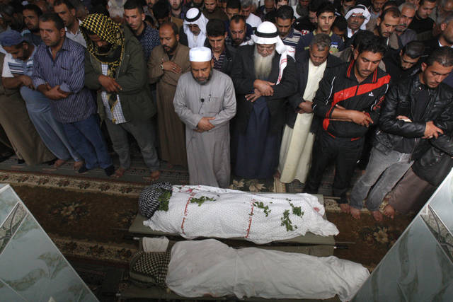 Palestinians pray over the bodies of farmers Amin Bashir, 40, and Tamer Bashir, 30, during their funeral in Deir Al Balah, central Gaza Strip, Monday, Nov. 19, 2012. The Palestinian civilian death toll mounted Monday as Israeli aircraft struck densely populated areas in the Gaza Strip in its campaign to quell militant rocket fire menacing nearly half of Israel's population. (AP Photo/Adel Hana)