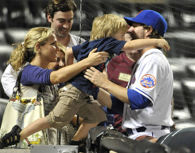 New York Mets' pitcher R.A. Dickey is greeted by his wife, Anne,  and son, Eli, 3, after the Mets' 5-0 victory over the Detroit Tigers in a baseball game Wednesday, June 23, 2010, in New York. Dickey pitched eight innings. (AP Photo/Kathy Kmonicek)