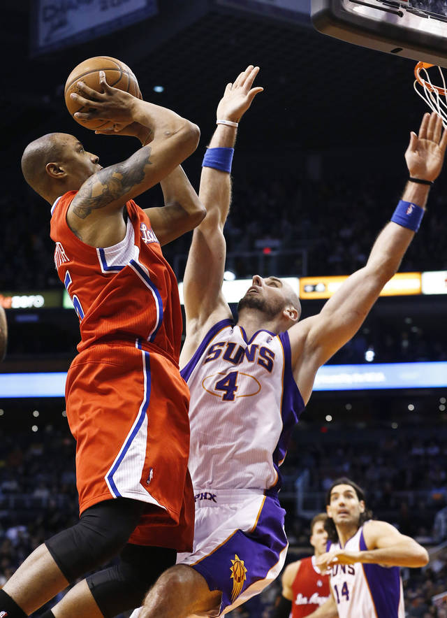 Los Angeles Clippers&#039; Caron Butler, left, drives to the basket to score against Phoenix Suns&#039; Marcin Gortat (4), of Poland, during the first half in an NBA basketball game on Thursday, Jan. 24, 2013, in Phoenix. (AP Photo/Ross D. Franklin)
