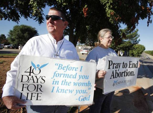 "Mark Daly and Deborah Krisch hold signs at a ""40 Days for Life"" prayer vigil outside the Outpatient Services for Women clinic at 6112 NW 63 in Warr Acres.  <strong>Steve Gooch - The Oklahoman</strong>"