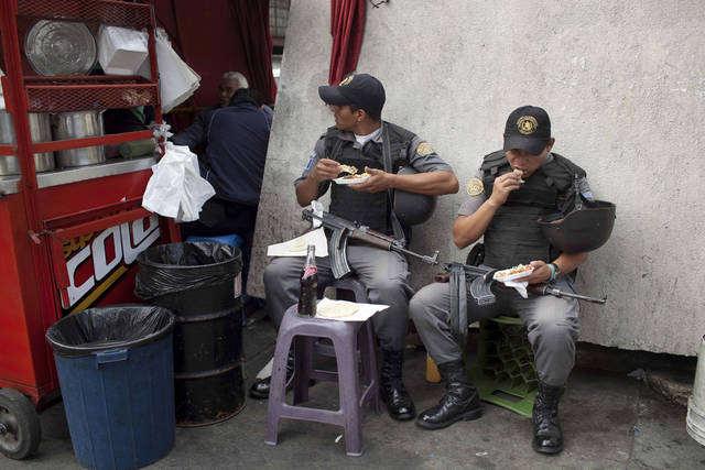 In this picture taken on Monday, July 25, 2011, prison service guards eat breakfast after escorting prisoners to court in Guatemala City. Guatemala City is a place where people live in fear. Dire poverty, gang violence and drug trafficking, and the failure of the government to provide a safety net, have contributed to the creation of a society where people isolate themselves from each other and make sure others keep their distance and where many seek solace in religion.(AP Photo/Rodrigo Abd)