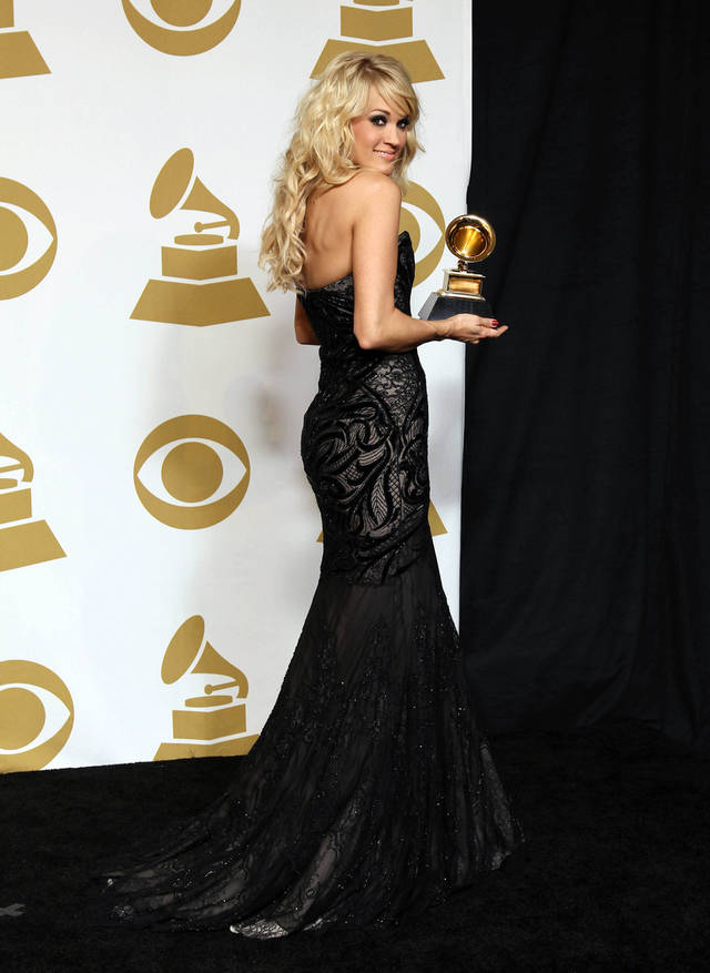 "Carrie Underwood poses backstage with the award for best country solo performance for ""Blown Away"" at the 55th annual Grammy Awards on Sunday, Feb. 10, 2013, in Los Angeles. (Photo by Matt Sayles/Invision/AP) ORG XMIT: CASH197"