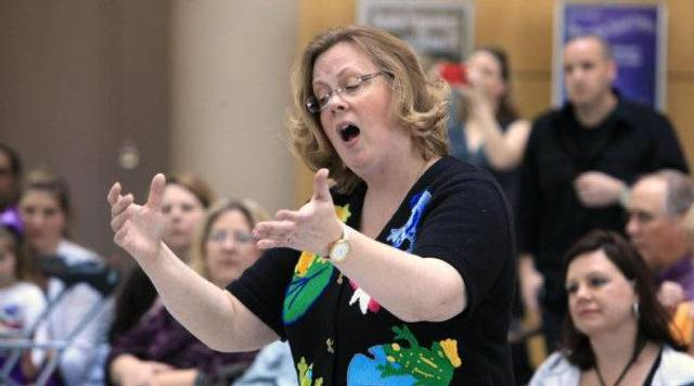 Choir director Lisa Cochrane conducts the Cleveland Choraleers from Cleveland Elementary School during Noon Tunes at the downtown library in Oklahoma City. Noon Tunes performances are free and happen every Thursday. <strong>PAUL B. SOUTHERLAND - THE OKLAHOMAN</strong>