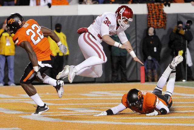 Oklahoma's Tress Way (36) is hit by Oklahoma State's Joe Aska Jr. (22) on a punt during the Bedlam college football game between the Oklahoma State University Cowboys (OSU) and the University of Oklahoma Sooners (OU) at Boone Pickens Stadium in Stillwater, Okla., Saturday, Dec. 3, 2011. Photo by Chris Landsberger, The Oklahoman