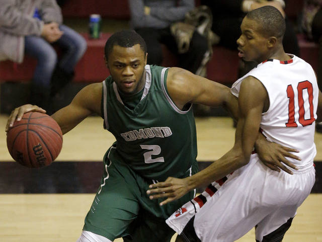 Edmond Santa Fe's Jaylin Johnson drives around Terrell Williams of Mustang during a boys high school basketball game in Mustang, Okla., Tuesday, Jan. 15, 2013. Photo by Bryan Terry, The Oklahoman