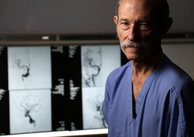 Dr. Timothy Tytle stands Friday in front Mario  Guzman�s images before and after surgery for an aneurysm at Mercy Hospital in Oklahoma City.  Photo by Bryan Terry, The Oklahoman