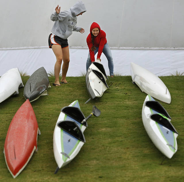 Members of the Washington Huskies team turn over kayaks to make adjustments to the seats.  Regatta Festival on the Oklahoma River in the Boat District,  Saturday,  Sep. 29, 2012. The event ends Sunday. Photo by Jim Beckel, The Oklahoman.