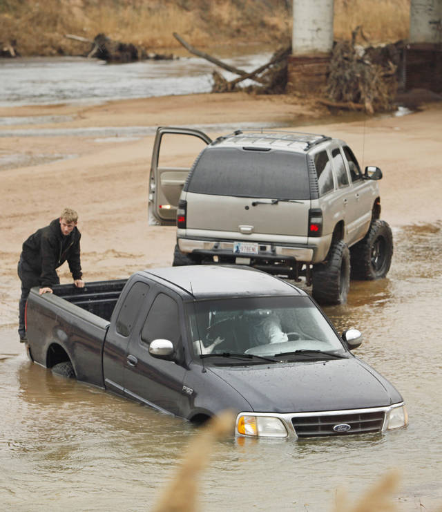 An off-road driver under the Canadian River Bridge at I-35 and State Highway 9 tries to retrieve his pickup before the river rises as rain passes through the area on Friday, Feb. 3, 2012, in Norman, Okla.  The vehicle became stuck around 10 a.m.  Photo by Steve Sisney, The Oklahoman