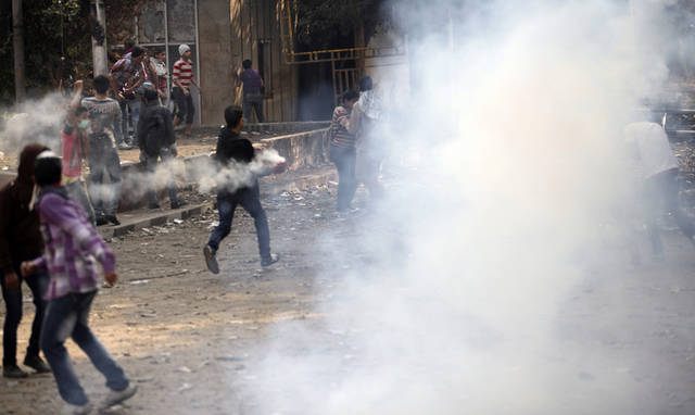 Egyptians clash with security forces and attempt to throw back tear gas canisters fired at them near Tahrir square, where an opposition rally has been called for to voice rejection of President Morsi's seizure of near absolute powers, in Cairo, Egypt, Tuesday, Nov. 27, 2012. The Health Ministry said about 444 people have been wounded nationwide, including 49 who remain hospitalized, since the clashes erupted on Friday, according to a statement carried by the official news agency MENA. (AP Photo/Thomas Hartwell)