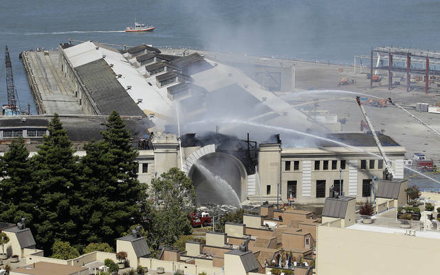 "Firefighters with the San Francisco Fire Department battle a fire at Pier 29 on the waterfront in San Francisco, Wednesday, June 20, 2012. Fire Department spokeswoman Mindy Talmadge says more than 100 firefighters are trying to ""surround the fire and drown it out."" Talmadge says no injuries have been reported. (AP Photo/Jeff Chiu)"