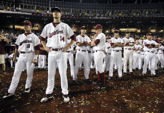 South Carolina players, including Evan Beal (14), watch as Arizona players celebrate their 4-1 victory in Game 2 to win the NCAA College World Series baseball finals in Omaha, Neb., Monday, June 25, 2012. (AP Photo/Dave Weaver)