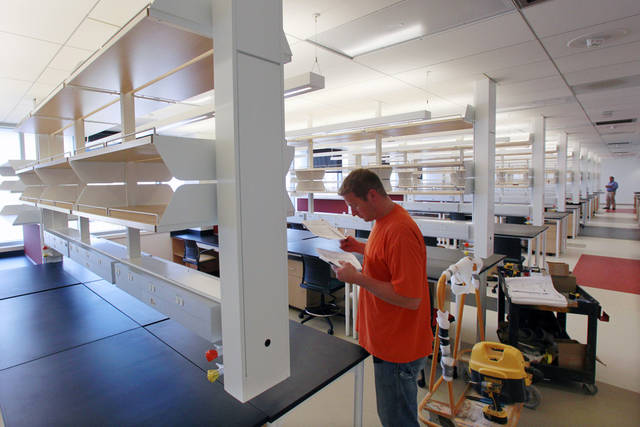 In this Tuesday, July, 17, 2012 photograph, a worker prepares a research laboratory at the new Cooper Medical School of Rowan University, as finishing details were still in the works for the school's $139 million building in downtown Camden, N.J. The upstart medical school in one of the nation's most impoverished cities aims to do more than simply add to supply of doctors, but to use new training methods to get students interacting with patients immediately in hopes of improving the health of the city. (AP Photo/Mel Evans)