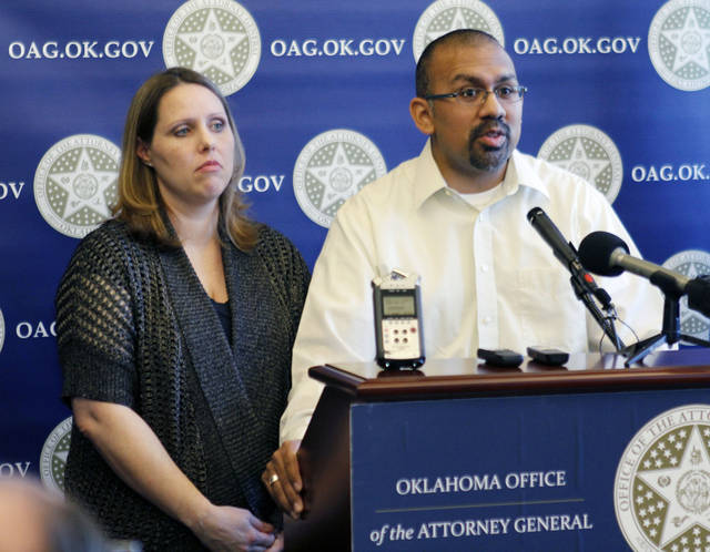 Melissa and Zachary Zuniga of Tulsa talk to reporters as Attorney General Scott Pruitt holds a press conference at the Attorney General's Office in Oklahoma City. The Zunigas were the first to receive compensation from Oklahoma's mortgage settlement with five big lenders, separate from one struck by the federal government and other 49 states. <strong>PAUL HELLSTERN - The Oklahoman</strong>