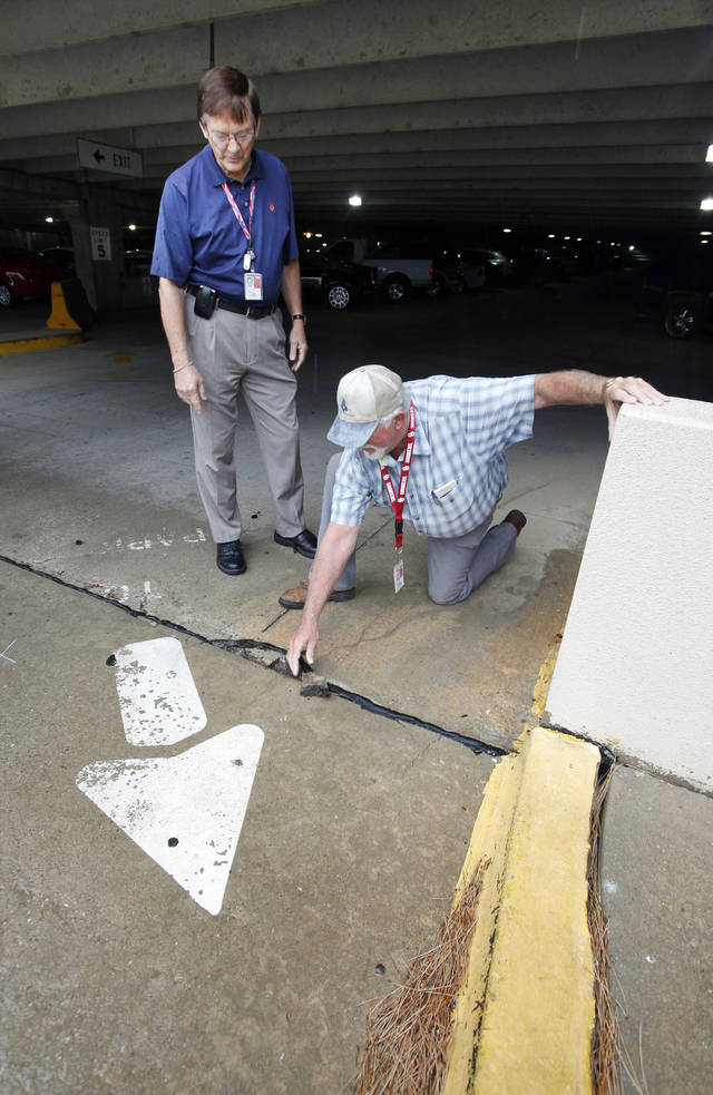 Don Jones, airport facility manager, and Rdell McMahan, airport construction manager, look at deteriorating material inside a parking garage at Will Rogers World Airport.