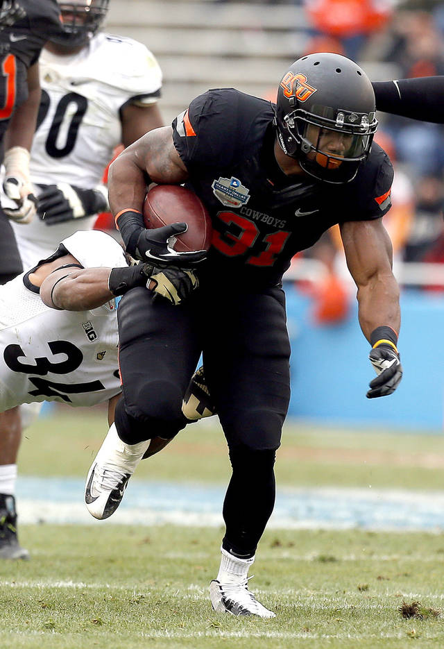 Oklahoma State's Jeremy Smith (31) gets by Purdue's Max Charlot (34) during the Heart of Dallas Bowl football game between the Oklahoma State University (OSU) and Purdue University at the Cotton Bowl in Dallas,  Tuesday,Jan. 1, 2013. Photo by Sarah Phipps, The Oklahoman