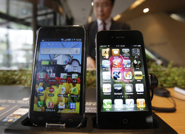 FILE-In this Friday, April 22, 2011, file photo, Samsung Electronics' Galaxy S, left, and Apple's iPhone 4 are displayed at the headquarters of South Korean mobile carrier KT in Seoul, South Korea, Friday. In a preliminary move, a federal judge denied Friday, Sept. 14, 2012, Samsung�s request for a ban on imports of the iPhone, iPad and iPod. A judge at the International Trade Commission in Washington ruled Friday that Apple doesn�t violate four Samsung patents. (AP Photo/Ahn Young-joon, File)