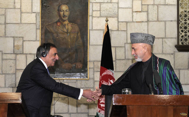 U.S. Defense Secretary Leon Panetta, left, shakes hands with Afghanistan President Hamid Karzai, right, during their joint press conference at the Presidential Palace in Kabul, Afghanistan, Thursday, Dec. 13, 2012. (AP Photo/Susan Walsh, Pool)