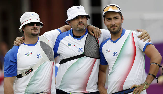 From left, Italy's Marco Galiazzo, Michele Frangilli and Mauro Nespoli hug after a semifinal win over Mexico in the team archery category during the 2012 Summer Olympics, Saturday, July 28, 2012, in London. (AP Photo/Marcio Jose Sanchez)