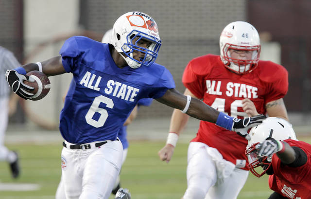 East's Justin Fogle pushes off West defenders for a gain during their ICA All-State football game at Jenks, OK July 30, 2010. MICHAEL WYKE/Tulsa World