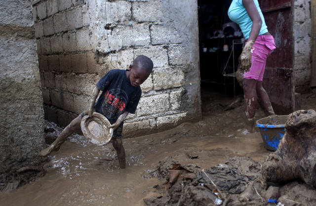 Winsky Pierre, left, 5, helps to drain mud from his flooded house after the passing of Tropical Storm Isaac in Port-au-Prince, Haiti, Sunday Aug. 26, 2012. The death toll in Haiti from Tropical Storm Isaac has climbed to seven after an initial report of four deaths, the Haitian government said Sunday. (AP Photo/Dieu Nalio Chery) ORG XMIT: PAP116
