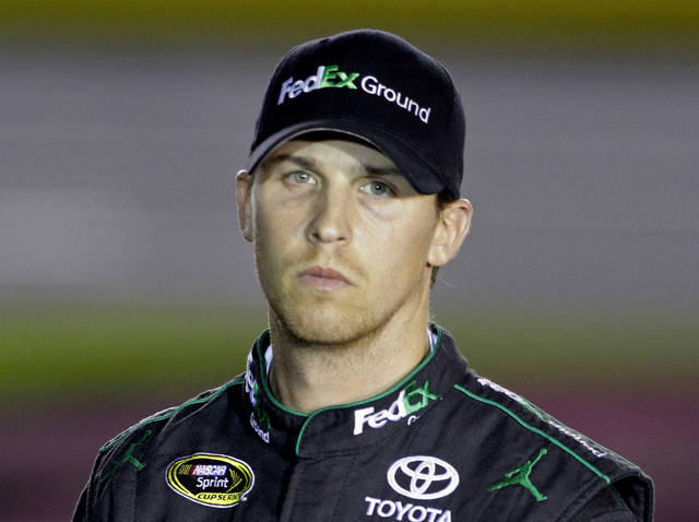 FILE - This is an Oct. 11, 2012 file photo showing Denny Hamlin waiting during qualifying for the NASCAR Bank of America 500 Sprint Cup series auto race in Concord, N.C. Chase contender Hamlin crashed during testing Thursday, Oct. 18, 2012 at Kansas Speedway and remains under observation after visiting the infield care center. (AP Photo/Chuck Burton, File)