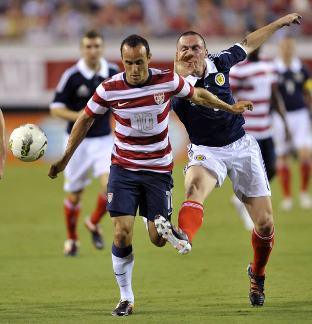 United States' Landon Donovan (10) is tripped up by Scotland's Scott Brown, right, during the first half of an exhibition soccer match, Saturday, May 26, 2012, in Jacksonville, Fla. United States won 5-1. (AP Photo/The Florida Times-Union, Will Dickey)