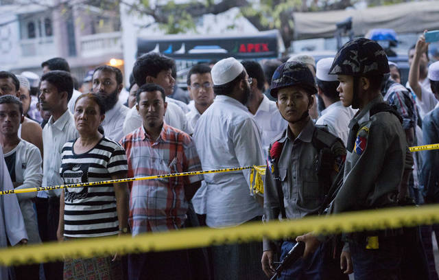 Muslim people gather out side a mosque after a fire as Police officers stand guard in Yangon, Myanmar, Tuesday, April 2, 2013. Police in Myanmar said 13 children died when an electrical fire broke out at the mosque in the country's largest city. (AP Photo/Gemunu Amarasinghe)