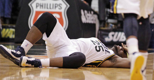 Utah Jazz center Al Jefferson (25) falls to the floor after being injured in the fourth quarter of an NBA basketball game against the Orlando Magic, Wednesday, Dec. 5, 2012, in Salt Lake City. The Jazz won 87-81. (AP Photo/Rick Bowmer)