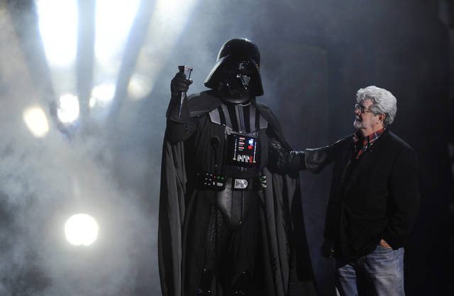 "FILE - In this Oct. 15, 2011 file photo, ""Darth Vader"" accepts the Ultimate Villain award from ""Star Wars"" creator George Lucas during the 2011 Scream Awards, in Los Angeles. A decade after George Lucas said ""Star Wars"" was finished on the big screen, a new trilogy is destined for theaters after The Walt Disney Co. announced Tuesday, Oct. 30, 2012, that it was buying Lucasfilm Ltd. for $4.05 billion. (AP Photo/Chris Pizzello, File)"