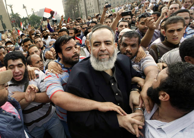 FILE - In this Friday, Oct. 28, 2011 file photo, Egyptian Muslim cleric and candidate for the Egyptian presidency Hazem Salah Abu Ismail, center, is guarded by his supporters as he enters Tahrir Square during a protest against the ruling military council, in Cairo, Egypt. Internal divisions are threatening to unravel Egypt�s second biggest political party, the political arm of the ultraconservative Salafis, the country�s most hardline Islamist movement. The party came out of nowhere after Mubarak�s fall to win the second largest number of seats in parliament, demonstrating the hidden strength of Salafis on the street. But now its leaders are split over whether Muslim clerics or more pragmatic politicians should be steering the movement. (AP Photo/Amr Nabil, File)