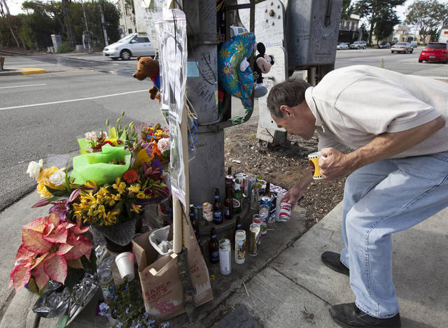 Tim Swanson checking a memorial for victim, 31-year-old Phillip Moreno is shown in Torrance, Calif., Tuesday, Nov. 27, 2012. Moreno was struck late Saturday by a car driven by Sherri Wilkins. Los Angeles County prosecutors have filed murder and drunken-driving charges against Wilkins, a substance abuse counselor, who allegedly struck Moreno and drove for more than two miles with the dying victim on the hood of her car. Moreno died at a hospital. (AP Photo/Damian Dovarganes)