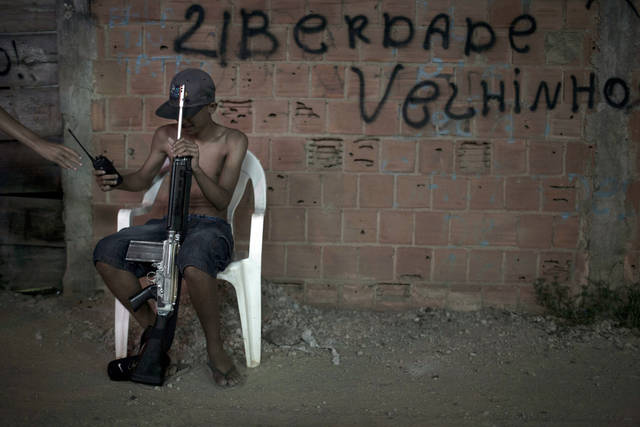"In this photo taken Dec. 8, 2012, a young drug dealer sitting on a chair holds a weapon and a two-way radio at a slum in western Rio de Janeiro, Brazil. The South American country began experiencing a public health emergency in recent years as demand for crack boomed and open-air ""cracolandias,"" or crack lands, popped up in the sprawling urban centers of Rio and Sao Paulo, with hundreds of users gathering to smoke the drug. The federal government announced in early 2012 that more than $2 billion would be spent to fight the epidemic, with the money spent to train local health care workers, purchase thousands of hospital and shelter beds for emergency treatment, and create transitional centers for recovering users. The graffiti reads in Portuguese ""Freedom old man."" (AP Photo/Felipe Dana)"