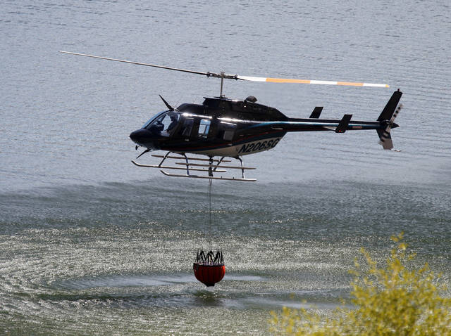 A helicopter with a water bucket dips into Rockport Reservoir to drop water on hot spots about two miles to the south of the wildfire that started Tuesday and destroyed a dozen homes in the Rockport Estates in Wanship, Utah. Helicopters flew hundreds of water drops to fight the fire. The lightning-sparked blaze was among several in the West where fires have devoured dry grass and brush and burned to the edges of small communities. (AP Photo/The Salt Lake Tribune, Al Hartmann)  DESERET NEWS OUT; LOCAL TV OUT; MAGS OUT