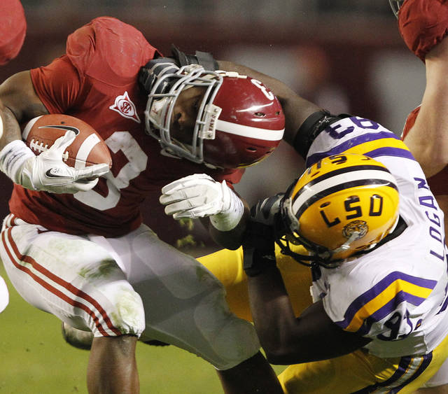 LSU defensive tackle Bennie Logan (93) wraps up Alabama running back Trent Richardson (3) during the second half of an NCAA college football game Saturday, Nov. 5, 2011, in Tuscaloosa, Ala. (AP Photo/Butch Dill) ORG XMIT: ALMS142