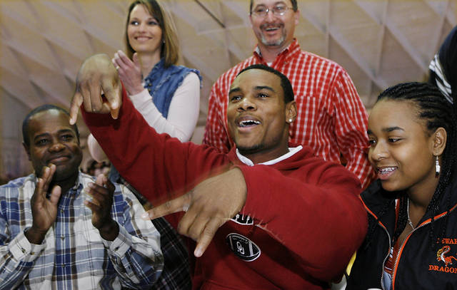 Dewar defensive back Ronnel Lewis flashes the upside down 'Horns gesture as he responds to loud applause from family, friends and student body who watched him sign letter of intent to play football at the University of Oklahoma during a school-wide assembly in the school's gym Wednesday morning, February 4, 2009.  BY JIM BECKEL, THE OKLAHOMAN