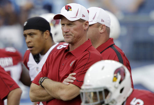 FILE - In this file photo taken Aug. 23, 2012, Arizona Cardinals head coach Ken Whisenhunt, center, watches his players warm up before an NFL football preseason game against the Tennessee Titans in Nashville, Tenn. Whisenhunt waited until the end of the preseason to choose a starting quarterback as neither Kevin Kolb nor John Skelton distinguished themselves in practice or in games. (AP Photo/Wade Payne, File)