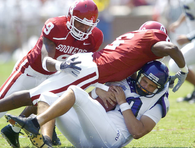Oklahoma Sooners defenders Keenan Clayton (9) and Jason Carter (6) tackle TCU punter Bryan Cortney as he tried to punt in the second half, in the 2005 season opener at  The Gaylord Family-Oklahoma Memorial Stadium, in Norman, Oklahoma Saturday, September 3, 2005.   By Jim Beckel/The Oklahoman