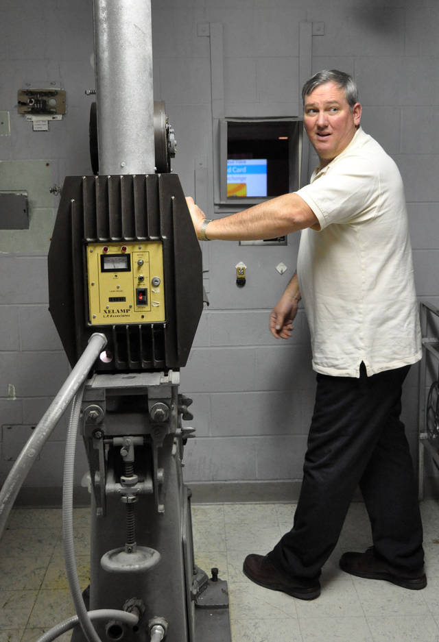 "Ron Reynolds, projectionist for the Ellsworth Air Force Base theater, prepares to start a reel showing ""Hotel Transylvania"" on the South Dakota film house's last day of operation, Saturday, Jan. 19, 2013. The Army and Air Force Exchange Service theater serving airmen and their families is one of 60 across the globe that's closing because it's too expensive to switch from 35 millimeter film prints to an all-digital projection format. (AP Photo/Dirk Lammers)"