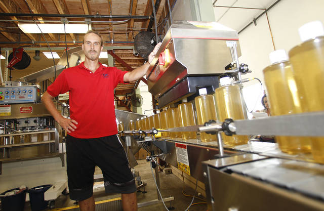 "David Bronner, of Dr. Bronner's Magic Soap, stands along side an assembly line where his ""Magic Soap"" is manufactured with a hemp oil as a key ingredient Monday, Oct. 8, 2012 in Escondido, Calif. Bronner has donated $50,000 to the campaign to legalize cultivation of hemp in the state of Washington. (AP Photo/Lenny Ignelzi)"