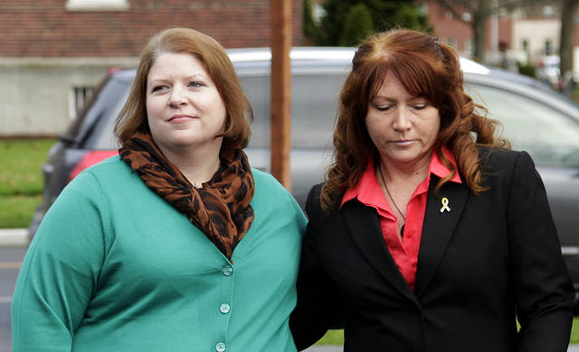 Kari Bales, left, stands with her sister, Stephanie Tandberg, right, as Stephanie prepares to read a statement to reporters Tuesday Nov. 13, 2012, outside the building housing a military courtroom on Joint Base Lewis McChord in Washington state, where a preliminary hearing ended Tuesday for Kari's husband, U.S. Army Staff Sgt. Robert Bales. Bales is accused of 16 counts of premeditated murder and six counts of attempted murder for a pre-dawn attack on two villages in Kandahar Province in Afghanistan in March of 2012. (AP Photo/Ted S. Warren)