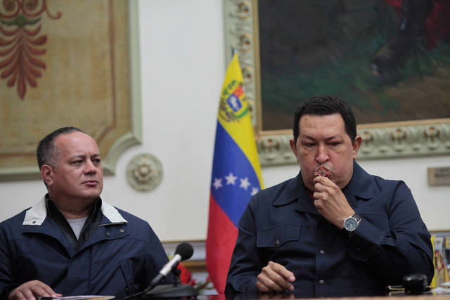 In this photo released by Miraflores Press Office, Venezuela's President Hugo Chavez , right, kisses a crucifix beside the President of the national Assembly Diosdado Cabello during a televised speech form his office at Miraflores Presidential palace in Caracas, Venezuela, Saturday, Dec. 8, 2012. Chavez announced Saturday night that his cancer has returned and that he will undergo another surgery in Cuba. Chavez, who won re-election on Oct. 7, also said for the first time that if his health were to worsen, his successor would be Vice President Nicolas Maduro.(AP Photo/Miraflores Press Office, Marcelo Garcia)