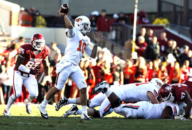 Oklahoma State's Clint Chelf (10) throws a pass and then becomes a receiver during the Bedlam college football game between the University of Oklahoma Sooners (OU) and the Oklahoma State University Cowboys (OSU) at Gaylord Family-Oklahoma Memorial Stadium in Norman, Okla., Saturday, Nov. 24, 2012. Photo by Steve Sisney, The Oklahoman
